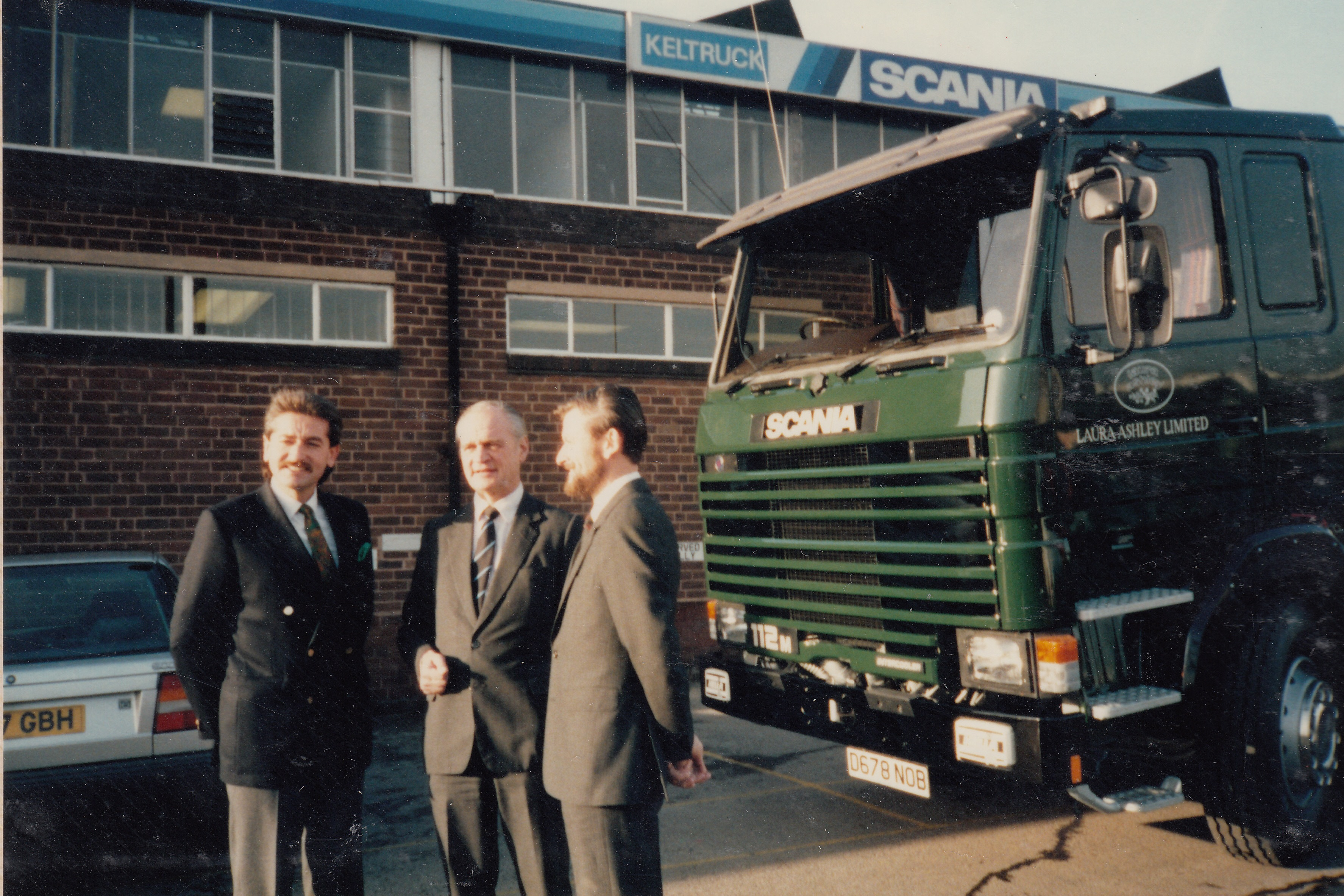 Chris Kelly (Managing Director & Dealer Principal), Anders Siewertz (Managing Director, Scania (Great Britain) Limited) & a Laura Ashley company representative celebrate the delivery of Keltruck's 1,000th Scania truck in August 1986.