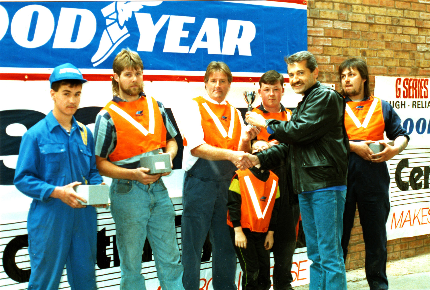 Ray Hingley of A. Hingley (Transport) Limited receives the winner's cup for the Scania wheel change competition for Telethon '90 from Keltruck's Chris Kelly on 19 May 1990.